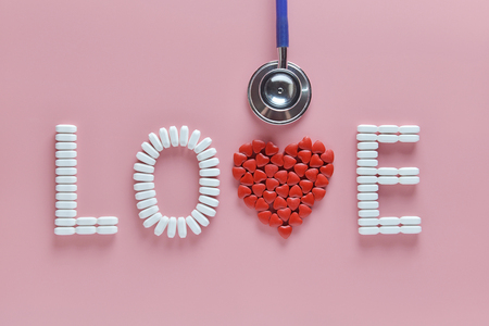 LOVE word made from medicine pills, red heart shape and stethoscope, on pink background. Concept of Valentine's Day or pharmacy, Medical.