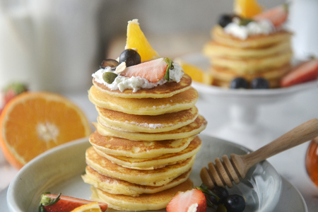 Close-up, Decorating a stack of pancakes by baker hands with blueberries, strawberries, orange and whipping cream on plate. Standard-Bild
