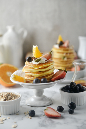 Beautiful dessert, fresh pancakes with blueberries, strawberries, orange, honey and whipping cream on plate. Concept of Cooking ingredients and method and plating, Dessert recipes and homemade. 写真素材