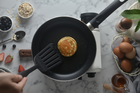 Flip the pancakes with a spatula. Concept of Cooking ingredients and method on white marble background, Dessert recipes and homemade.
