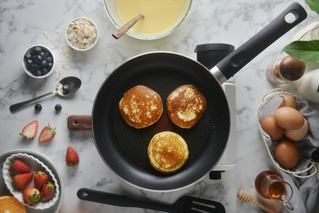 Pancakes onto the pan. Concept of Cooking ingredients and method on white marble background, Dessert recipes and homemade.