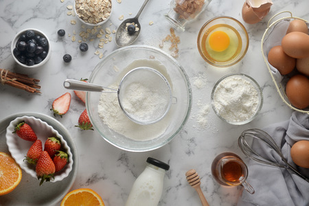 Making pancakes, cake, baking of baker hands pouring or sifting flour in bowl. Concept of Cooking ingredients and method on white marble background. Dessert recipes and homemade. 写真素材