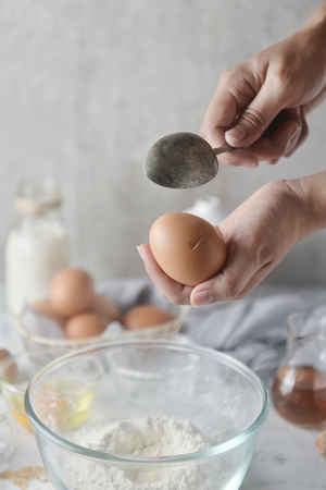 Baker hands using a spoon to crack an egg. Concept of Cooking ingredients and method in kitchen, Dessert recipes and homemade.