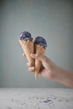 Women hand holding waffle cone with purple ice cream and decorated with chocolate sprinkles on plain background.