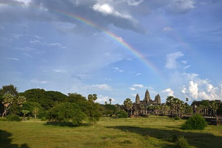 Angkor Wat on blue sky background with beautiful rainbow and forest in foreground