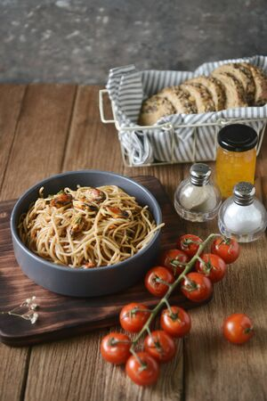 Tasty Italian spaghetti pasta with mussel, tomato, whole wheat bread and garnish on round dish and wooden plate for serving on wooden table background. side view, perspective, vertical, image Stock fotó