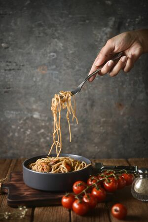 Spaghetti is pulled up by the fork in hand from dish and wooden plate for serving with homemade environment on classic, rustic background. side view, perspective, vertical, pouring shots, head on, image