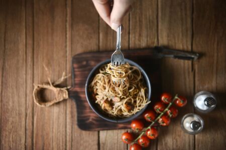 Spaghetti is pulled up by the fork in hand from dish and wooden plate for serving with homemade environment on classic, rustic background. top view, horizontal, pouring shots, image