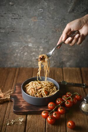 Spaghetti is pulled up by the fork in hand from dish and wooden plate for serving with homemade environment on classic, rustic background. side view, perspective, vertical, pouring shots, image