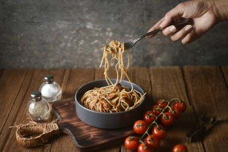 Spaghetti is pulled up by the fork in hand from dish and wooden plate for serving with homemade environment on classic, rustic background. side view, perspective, horizontal, pouring shots, image