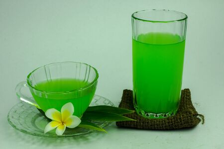 Glass of cold Pandan juice - healthy food against wood, With pandan green on a white background Stock Photo