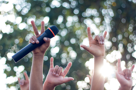 hand holding a single microphone against colourful background,singing contest.