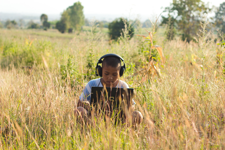 PHOP PHRA,TAKTHAILAND - JANUARY 27:An unidentified children using laptop wearing headphones on wild grass, she looked very focused laptop. on JANUARY 27,2016 in PHOP PHRA,TAKTHAILAND.