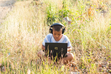 looked: PHOP PHRA,TAKTHAILAND - JANUARY 27:An unidentified children using laptop wearing headphones on wild grass, she looked very focused laptop. on JANUARY 27,2016 in PHOP PHRA,TAKTHAILAND.