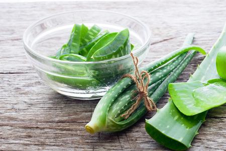 Folha fresca de Aloevera na tabela de madeira, aloés vera na tabela de madeira, ervas para a saúde, aloés Vera em um copo pequeno. Foto de archivo