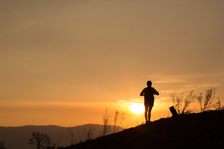 Woman backpacking to watch the sunset.Silhouette. Stock Photo