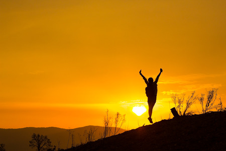 Woman backpacking to watch the sunset.Silhouette,Jumping glad.