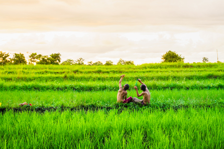 Twee kinderen schieten iets met een slingshot. In de rijstvelden