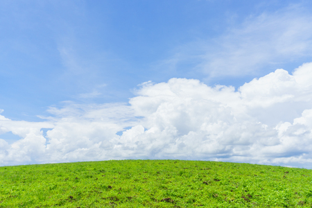 Green grassy hills and soft blue sky clouds.