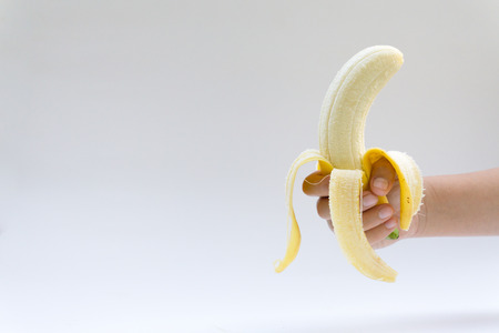 banana skin: The womans hand holds a banana, is isolated on a white background,Peel bananas on a white background. Stock Photo