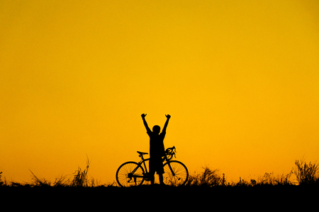 Silhouette of cyclist with friend in motion on the background of beautiful sunset.