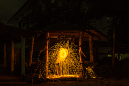 Burning steel wool spinned in the forest. Showers of glowing sparks from spinning steel wool. Stock Photo
