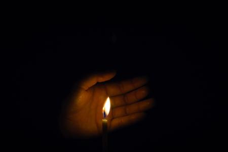 Die Hand, die die Kerzen im Dunkeln schützt. Standard-Bild