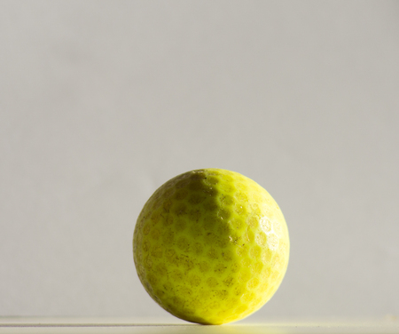 Old yellow golf ball on white backdrop.