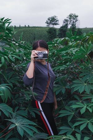 Young women travel on cassava fields, hold old cameras, take pictures.