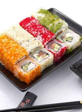 Sushi rolls in a black ceramic plate isolated on white