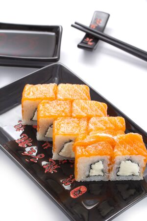 metallic seaweed: sushi rolls in a black ceramic plate isolated on white