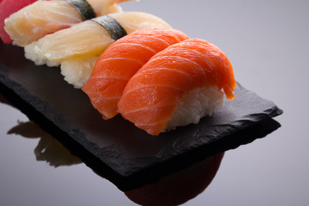 Sushi nigiri set on a stone plate over black background Stock Photo