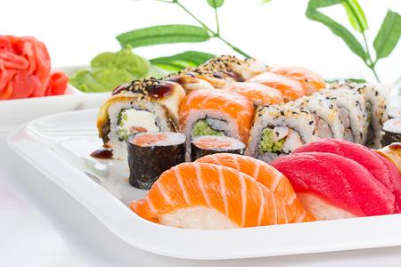 comida japonesa: Conjunto de sushi en un plato blanco sobre fondo blanco