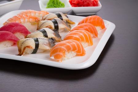 grig: Japanese cuisine. Set of sushi nigiri on white plate.
