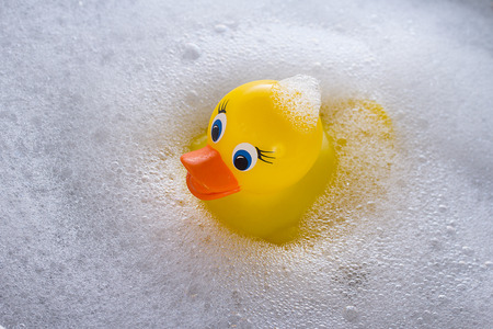 Yellow rubber duck floating in soap suds Zdjęcie Seryjne - 40887168