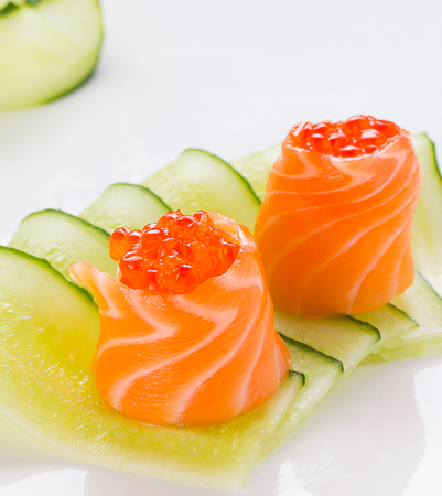 Rolled salmon with cucumber isolated on white background