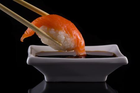 japanese foods: Salmon sushi nigiri in hopsticks with soy sauce over black background