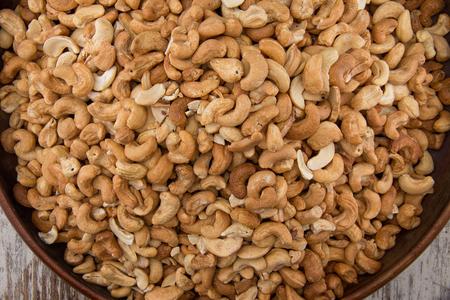 cashews: Raw cashews close-up in wooden bowl