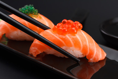 sushi chopsticks: Salmon sushi nigiri in chopsticks over black background