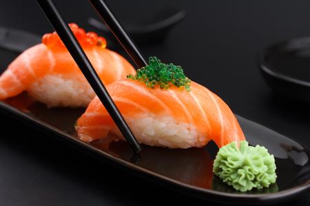 Salmon sushi nigiri in chopsticks over black background