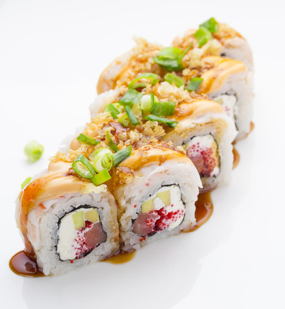 exotically: Sushi with shrimp avocado salmon and cheese strewed with green onion. Crunch Roll. With delicious sauces. Over white background.