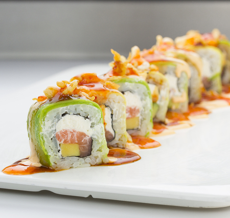 meat alternatives: Sushi with avocado salmon and cheese. Crunch Roll. With delicious sauces. On a plate over white background.