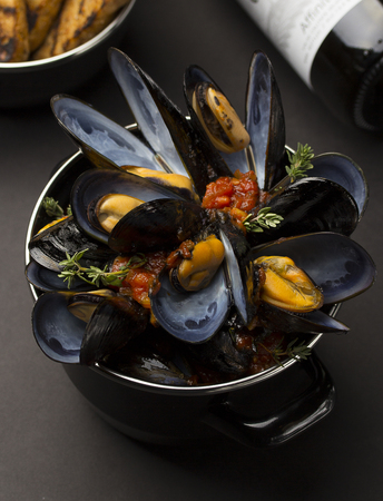 Mussels in copper cooking dish and French Baguette and wine over black background