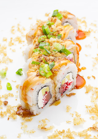 strewed: Sushi with shrimp avocado salmon and cheese strewed with green onion. Crunch Roll With delicious sauces Over white background.