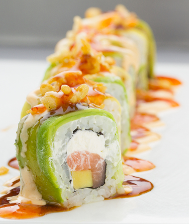 meat and alternatives: Sushi with avocado salmon and cheese. Crunch Roll With delicious sauces On a plate over white background.
