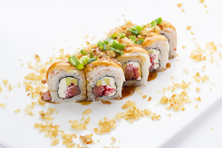 strewed: Sushi with shrimp avocado salmon and cheese strewed with green onion. Crunch Roll. With delicious sauces. On a plate over white background.