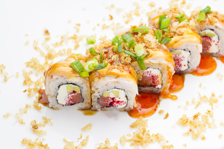 exotically: Sushi with shrimp avocado salmon and cheese strewed with green onion. Crunch Roll With delicious sauces Over white background.