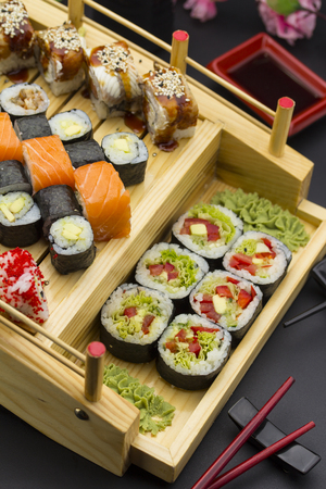 yummy: Sushi set with different fish on a wooden plate over black background