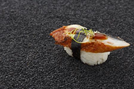 speciality: Eel sushi nigiri on black sesame background