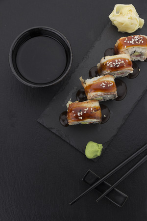 speciality: Eel sushi roll on a plate with ginger wasabi soy sauce and chopsticks over black background